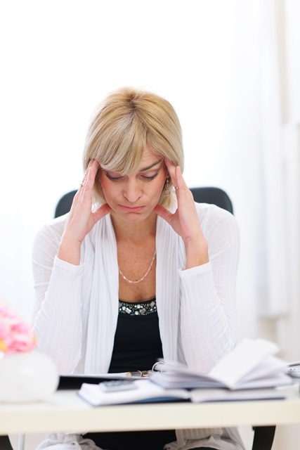 Stressed senior business woman sitting at office table