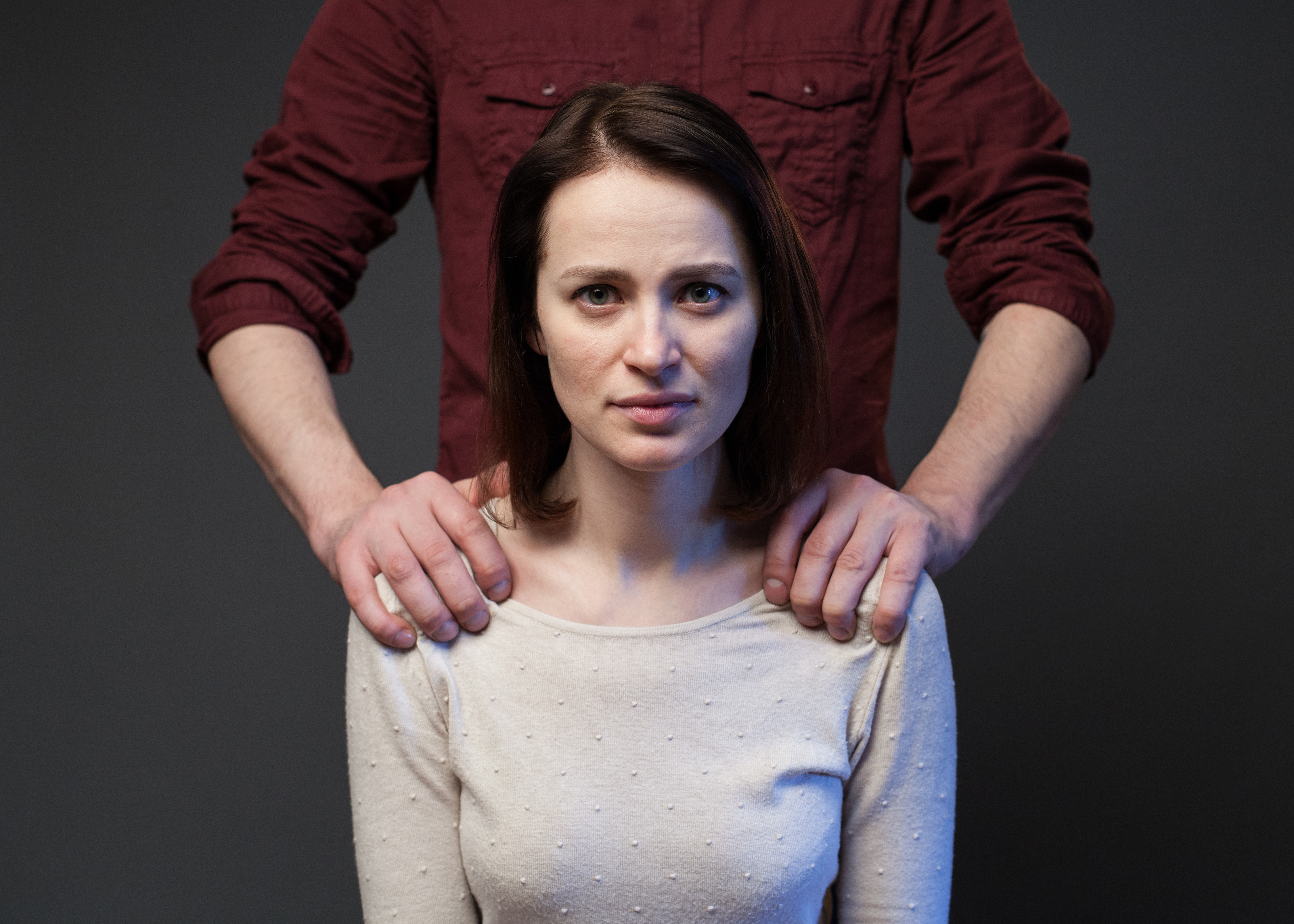 Family abuse – man's hands keeping woman's shoulders, gray background