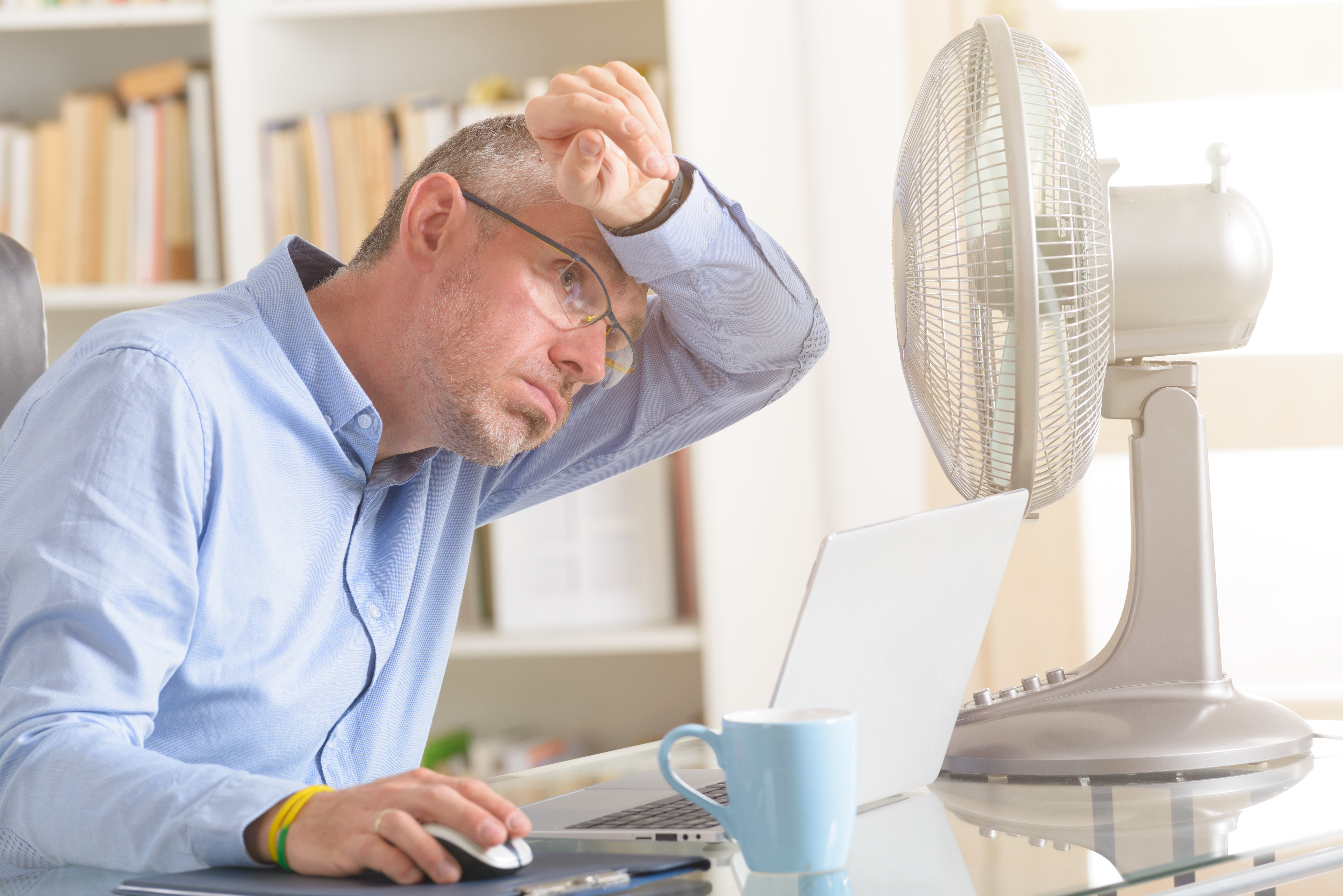 Man suffers from heat in the office